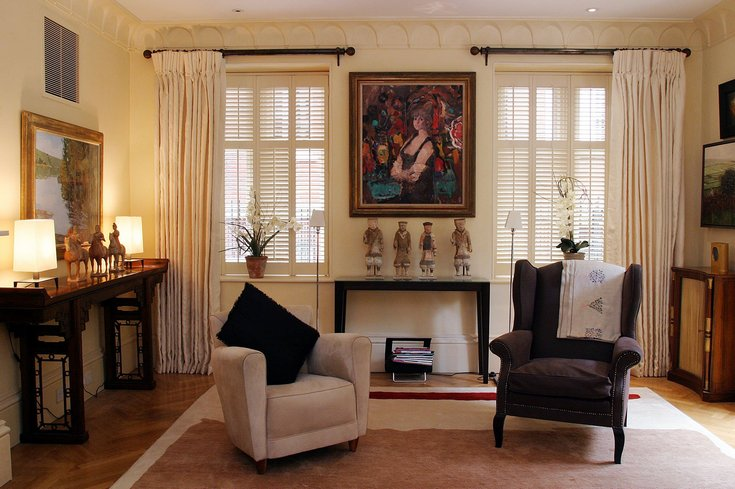 living room with two armchairs, cream open curtains and full height shutters covering the windows