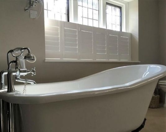 old style bath tub illuminated by the light coming through a window with cafe style bathroom shutters