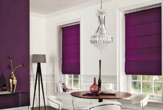 purple roman blinds matching the colour of the opposite wall in a white modern dining room with a round wooden table and modern white chairs