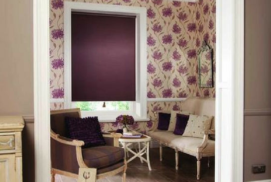 small vestibule with sofa and chairs and a little window with a purple roller blind matching the colour of the wall paper