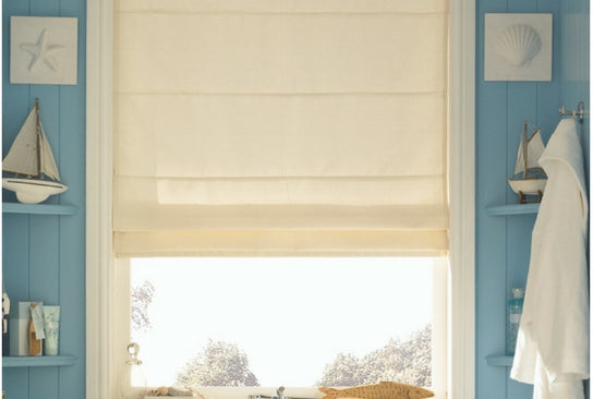 large window with beige roman blinds, wooden walls in light blue with shelf with ship models and books giving a marine feel