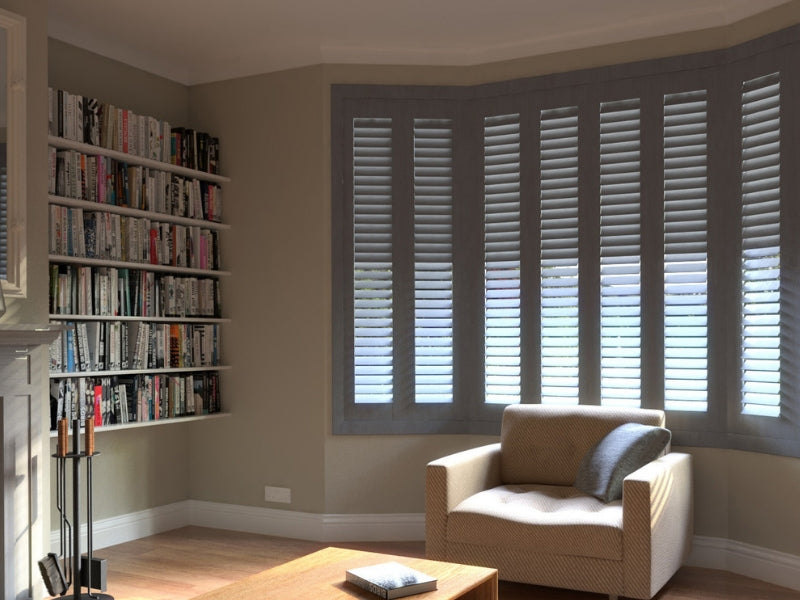 hardwood shutters in a bay window of a living room