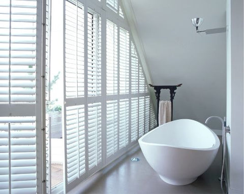narrow bathroom with sloping roof and large windows on one side covered with shutters