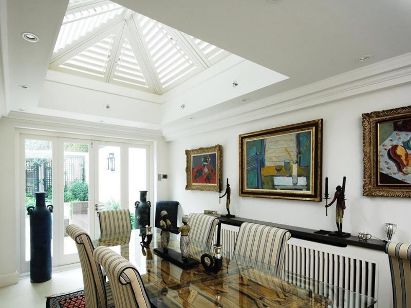 dining room with unusual shaped ceiling with window and shutters