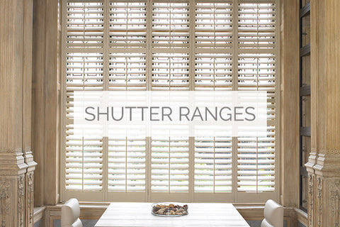 plantation shutters range sold in Wiltshire represented by an image of a dining room in pastel colour with pale brown window shutters in the background