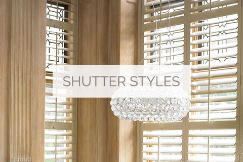 plantation shutter styles available for sale in Wiltshire, represented by an image of a room corner, with a large crystal chandelier and plantation shutters in the background mounted on the windows