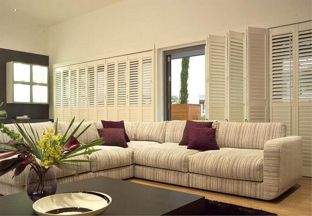 large living room shutters sliding open behind an l shaped modern sofa