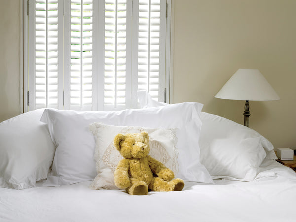 shutters matching the colour of the sofa and teddy bear on the sofa