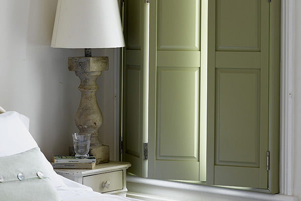 bedroom with light green solid shutters