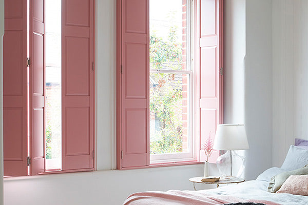 bedroom with solid shutters in pink matching the decor of the room