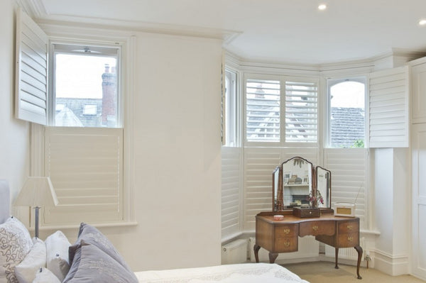 bedroom with two windows with tier on tier shutters, top half open