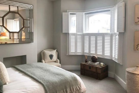 bedroom with bay window and white tier on tier shutters, with upper tier open