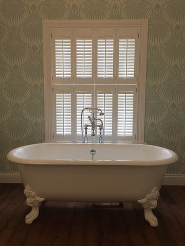bath tub in front of a window with closed shutters