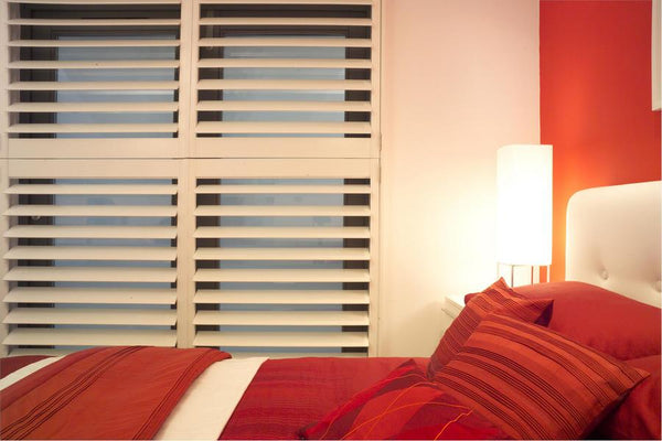 double bedroom with red covers matching the red walls and withe window shutters
