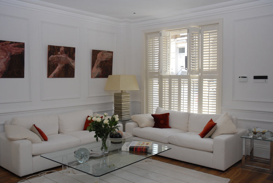 white living room, white corner sofa and white tier on tier living room shutters half open