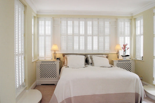 white bedroom with large window and white shutters