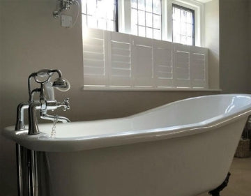 old style bath tub in a tiny bathroom white cafe style shutters on the window