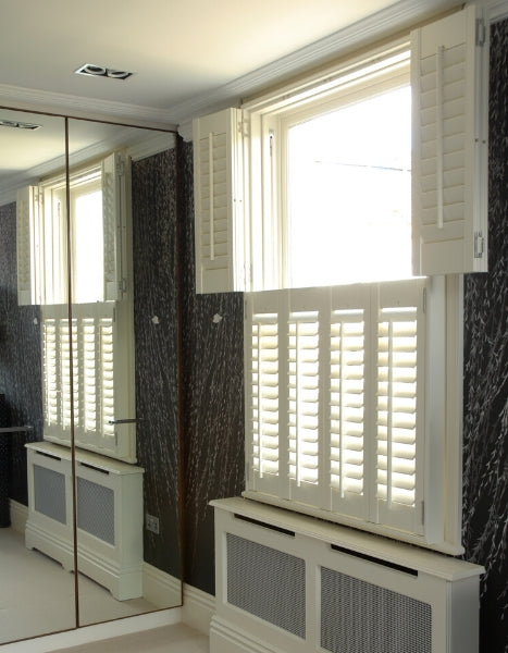 room with a mirrored wardrobe and white shutters on the window, top tier open