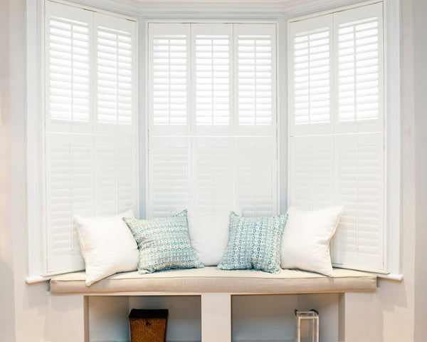 white half open shutters on a bay window with cream sofa in front with light coloured cushions