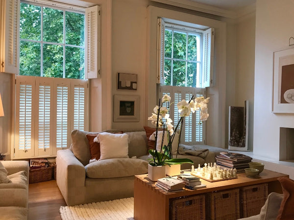 wooden shutters tier on tier in a living room with sofa ans wooden furniture