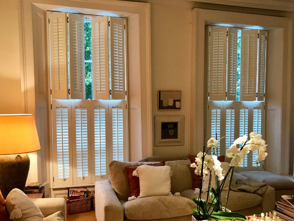 detail of half closed tier on tier wooden shutters in an elegant living room
