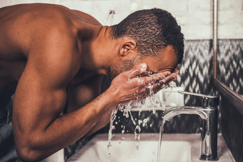 man washing face at sink to clean body hair