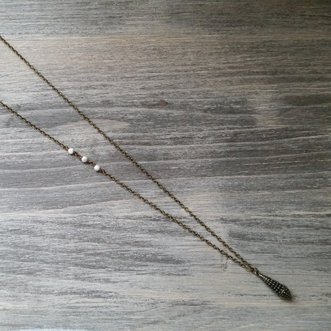 simple elegant long necklace with detailed hollow small teardrop pendant and mother of pearl beads. 33 inches