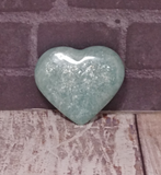 Hand carved gemstone heart from Madagascar on Wood grain background