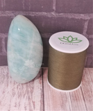 Amazonite gallet from Madagascar on wood grain background with thread spool size reference