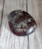 Natural purple and white gemstone gallet on wood grain background