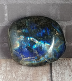 Iridescent gemstone on wood grain background Labradorite from Madagascar GGandJ.com