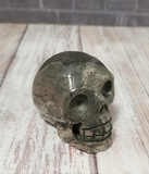 Hand carved gemstone skull from Brazil on Wood grain background