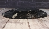 Side view of ammonite oval plate on wood grain background