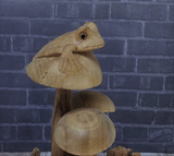 Close up of wood frog on mushroom statue