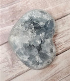 Celestite Gemstone from Madagascar heart on wood grain