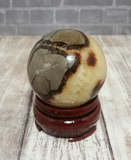 Gemstone Sphere Yellow Brown and Gray on Wood stand brick and woodgrain background GGandJ.com