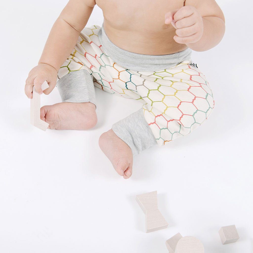 seated baby with multicolored drop-crotch pants