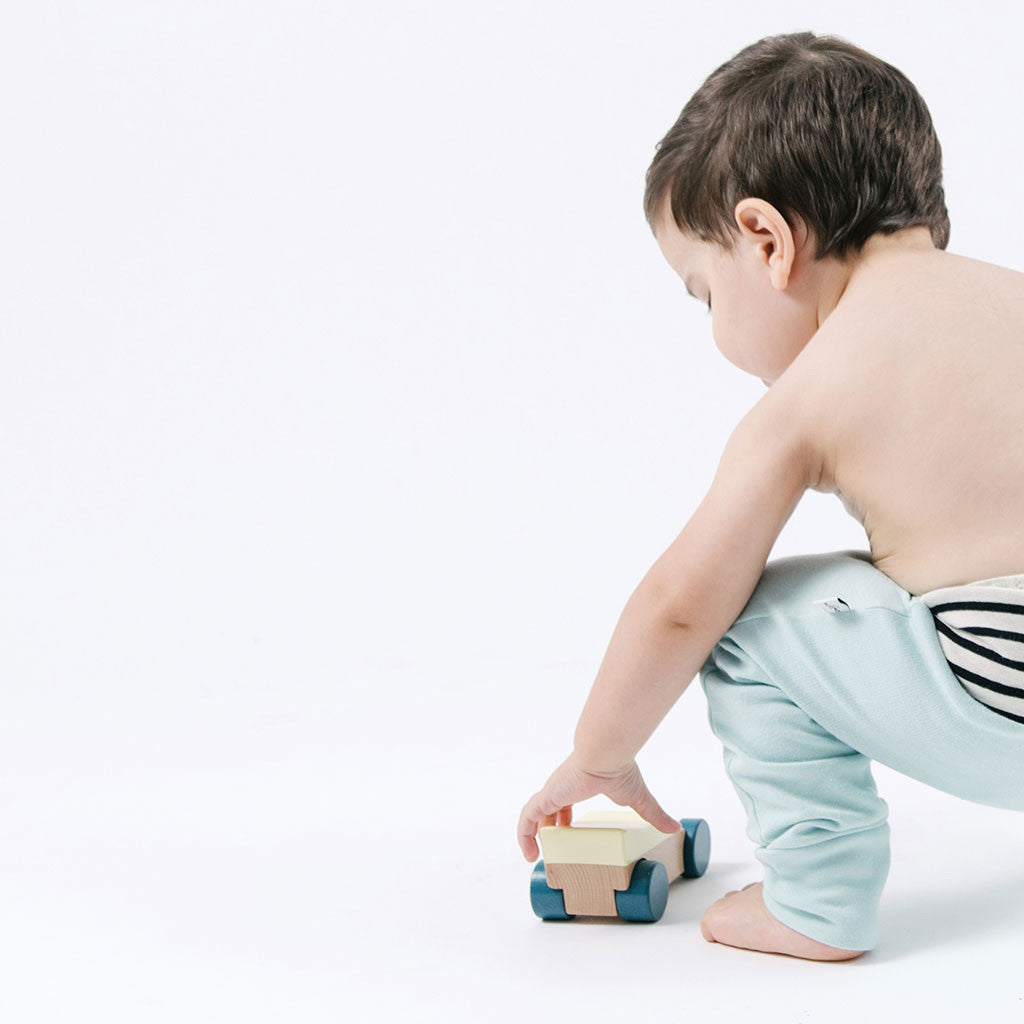 toddler in light blue pants playing with car toy
