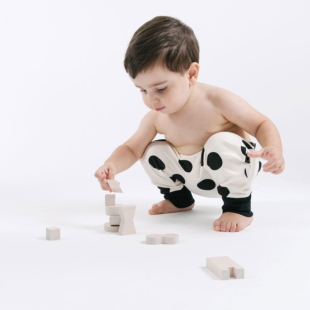 baby in white and black polka dots pants