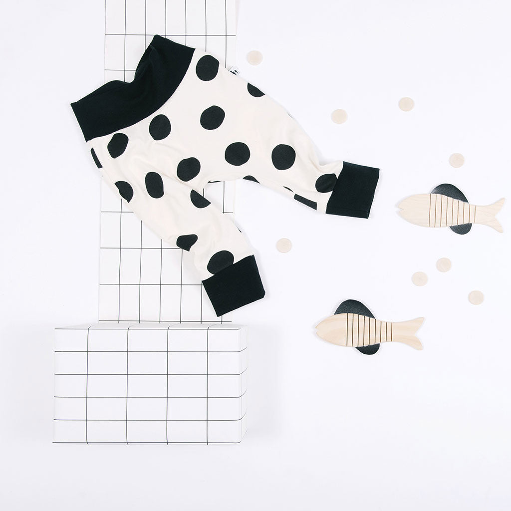 flat lay of white and black polka dots baby pants