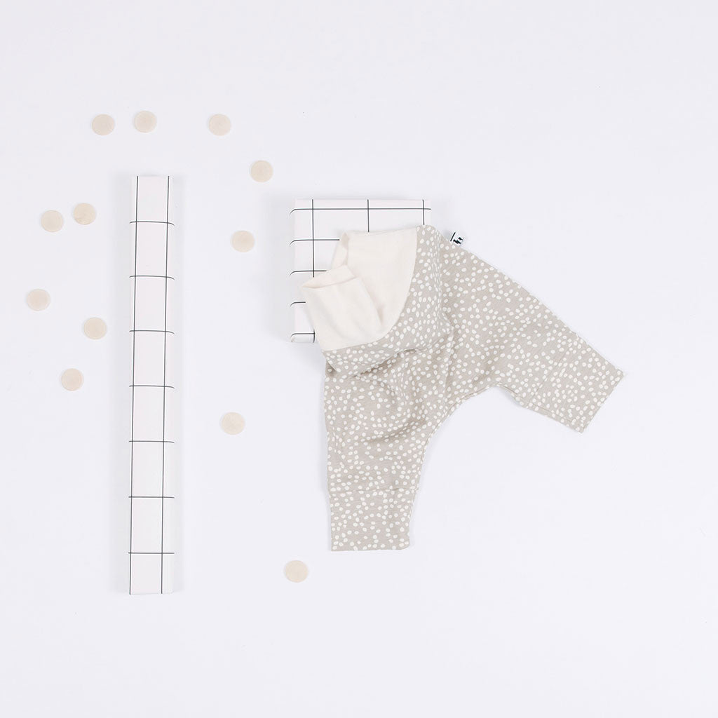 flat lay of sandbox baby pants with small white dots