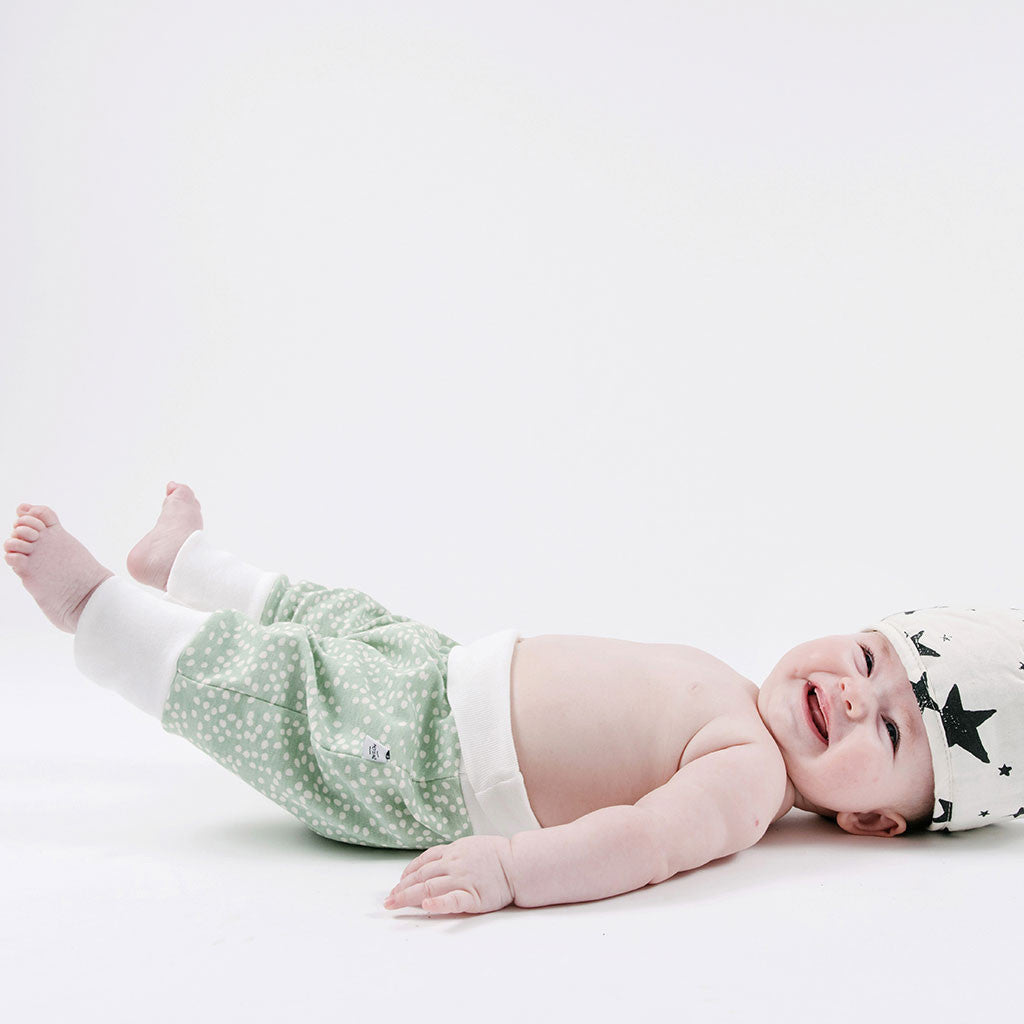 baby in mint with white dots pants and hat