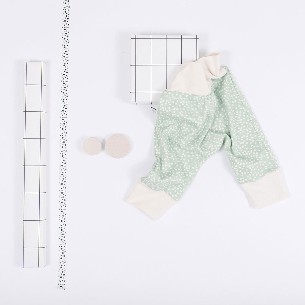 flat lay of unisex green with white dots baby drop-crotch pants