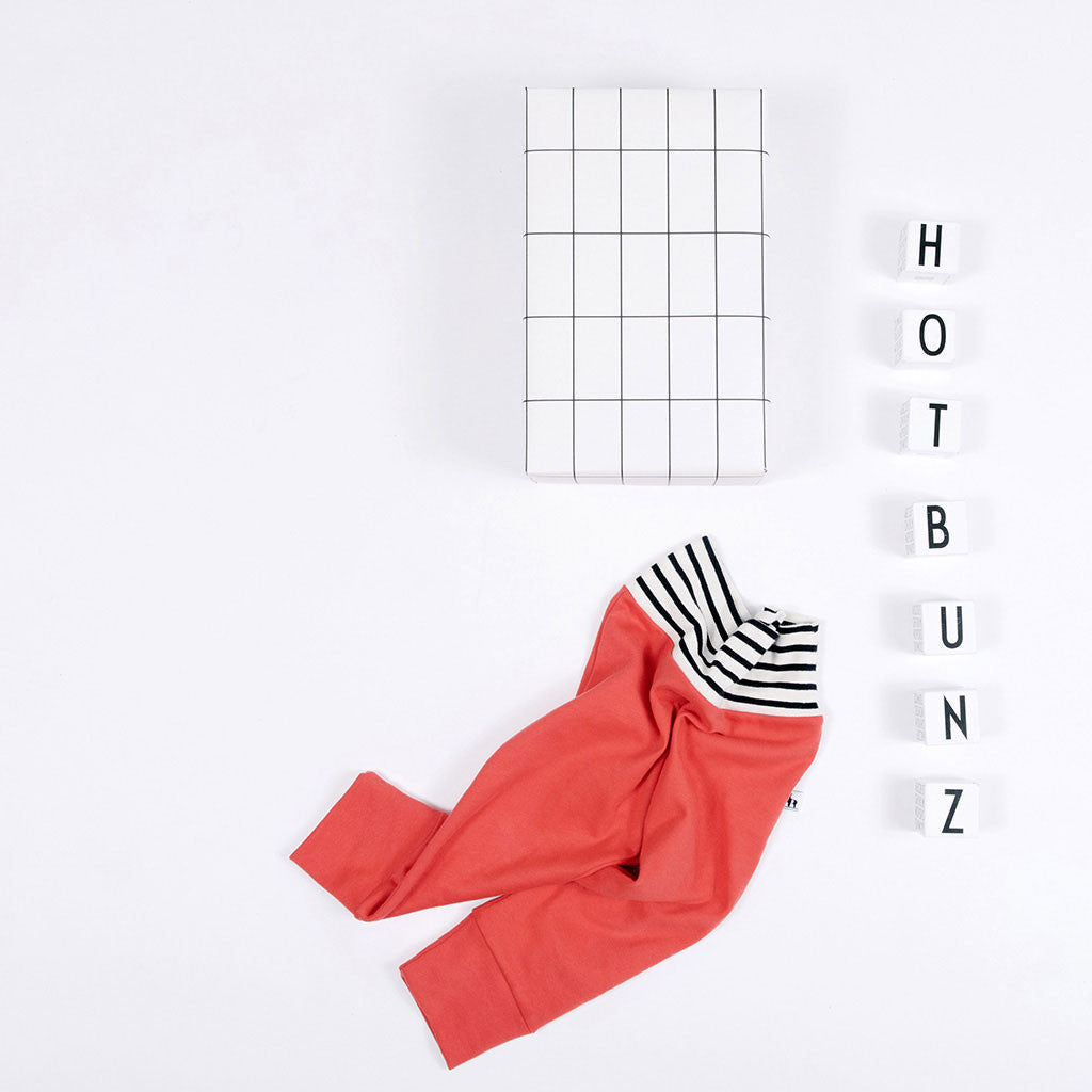 flat lay of red baby pants with stripe waistband