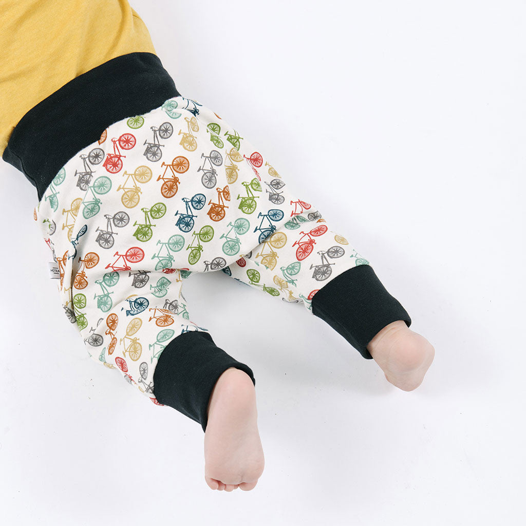 baby legs in multicolored pants with bicycles prints
