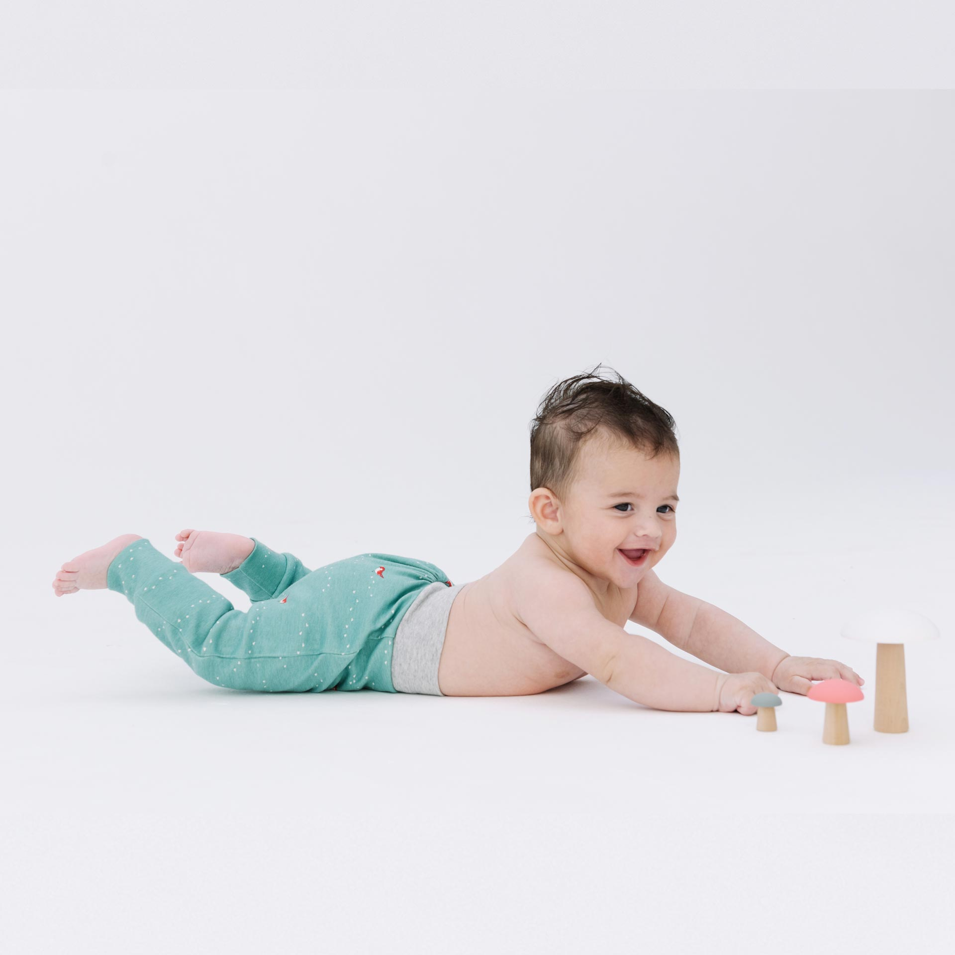 Baby with green pants playing on the floor