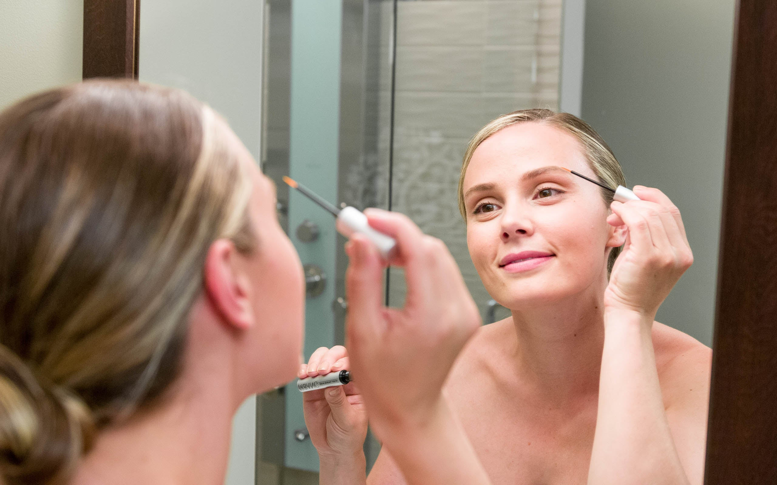 woman adding eyebrow serum to her eyebrows in front of a mirror