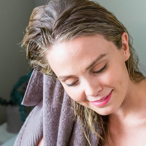 Woman towel drying her freshly washed hair