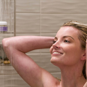 Woman in shower happily washing her hair