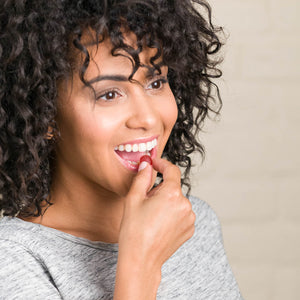 Woman happily placing Nourish Biotin Gummy into mouth